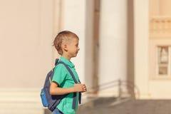 A criança bonito com mochila vai à escola Menino com backpak foto de stock