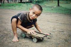 criança bonito com seu brinquedo favorito um carro de madeira imagem de stock royalty free