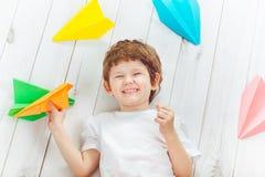 A criança bonito de sorriso com t-shirt branco guarda o avião alaranjado Imagem de Stock