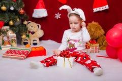 A criança bonito em um terno do coelho abre um presente do Natal Foto de Stock Royalty Free