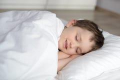 A criança bonito está dormindo na cama branca Fotos de Stock Royalty Free