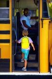A criança bonito está obtendo no ônibus, apronta-se para ir à escola Fotos de Stock Royalty Free