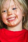 Criança bonito, feliz com a cara com cobertura em chocolate desarrumado Fotografia de Stock Royalty Free