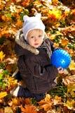 A criança bonito jogou com uma esfera azul em suas mãos Imagem de Stock Royalty Free