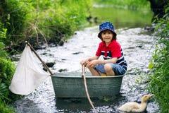 Criança bonito, menino, jogando com barco e patos em um rio pequeno Imagens de Stock