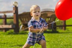 Criança bonito no luminoso com um balão vermelho Bebê engraçado que joga fora Modo do verão fotos de stock royalty free