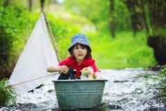 A criança bonito, o menino, jogando com barco e os patos em um pouco rive Imagem de Stock
