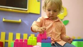 Criança bonito pré-escolar bonita que joga com multi blocos de apartamentos coloridos no jardim de infância Desenvolvimento infan filme
