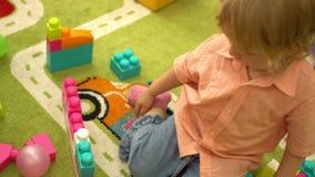 Criança bonito pré-escolar que joga com multi blocos de apartamentos coloridos no jardim de infância Desenvolvimento infantil no  filme