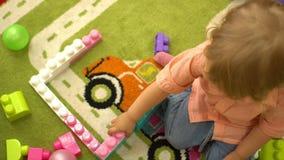 Criança bonito pré-escolar que joga com multi blocos de apartamentos coloridos no jardim de infância Educação no infantário filme