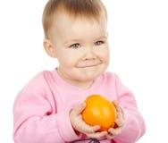 A criança bonito prende o mandarino Imagem de Stock Royalty Free