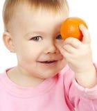 A criança bonito prende o mandarino Fotos de Stock Royalty Free