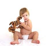 Criança bonito que abraça o brinquedo do tigre Fotografia de Stock Royalty Free