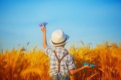 Criança bonito que anda no campo dourado do trigo em um verão ensolarado d imagem de stock