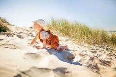 Criança bonito que climing acima em um monte arenoso na praia imagem de stock