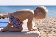 Criança bonito que descansa na praia sunbed Feriados do bebê do verão imagem de stock