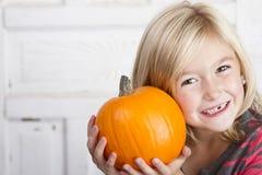 Criança bonito que guarda a abóbora pequena fotos de stock royalty free