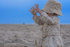 Criança bonito que joga com a areia na praia Fotografia de Stock Royalty Free