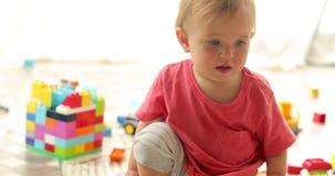 Criança bonito que joga com blocos do brinquedo vídeos de arquivo
