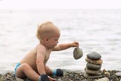 Criança bonito que joga com a pirâmide de pedra na pedra nova do ilusionista e da levitação da costa de mar Imagens de Stock