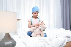 Criança bonito que joga o doutor com o brinquedo enchido na divisão de hospital foto de stock