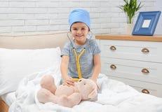 Criança bonito que joga o doutor com o brinquedo enchido na divisão de hospital imagem de stock royalty free
