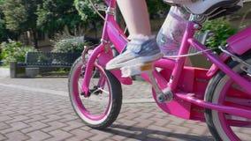 Criança bonito que monta uma bicicleta cor-de-rosa pequena vídeos de arquivo