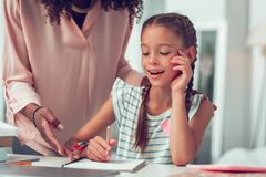 Criança bonito que pede a mãe a ajuda em relação aos trabalhos de casa da escola foto de stock royalty free