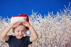 Criança bonito que tem o sorriso do divertimento da floresta coberto de neve foto de stock