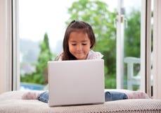 Criança bonito que usa o computador portátil Imagem de Stock Royalty Free