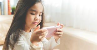 Criança bonito que usa um smartphone e sorrindo ao sentar-se no sofá fotografia de stock royalty free