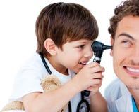 Criança bonito que verific as orelhas do doutor Fotos de Stock
