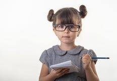 Criança bonito surpreendida nos monóculos, escrevendo no caderno usando o lápis, mantendo a boca largamente aberta fotografia de stock