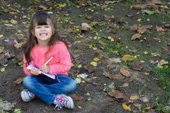 Criança bonito surpreendida nos monóculos, escrevendo no caderno usando o lápis, sorrindo fotografia de stock