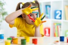 A criança bonito tem o divertimento que pinta suas mãos imagens de stock royalty free