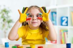 A criança bonito tem o divertimento que pinta suas mãos imagem de stock