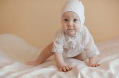 A criança bonito vestiu-se em crowling branco na cama Imagens de Stock Royalty Free