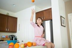 A criança brincalhão está na cozinha com laranjas foto de stock royalty free