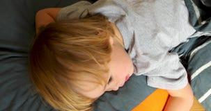 Criança cansado que encontra-se na cama e que olha avante vídeos de arquivo