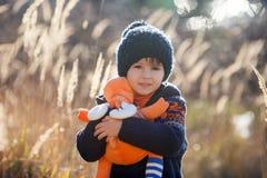 Criança caucasiano pequena bonito, menino, guardando o brinquedo macio, abraçando o foto de stock