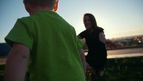 Criança caucasiano pequena do menino que joga e que ri com a mãe no parque no por do sol, lento-movimento vídeos de arquivo