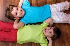 A criança caucasiano pequena que joga com lotes do plástico colorido obstrui interno Caçoe a camisa vestindo do menino e ter a cr Fotos de Stock