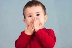A criança cobre a boca com as mãos Fotografia de Stock Royalty Free