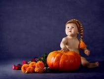 Criança com a abóbora grande sobre o fundo roxo. Fotos de Stock