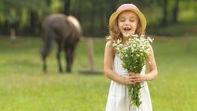 A criança com as flores selvagens em suas mãos aspirar-las Movimento lento vídeos de arquivo