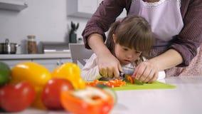 Criança com as necessidades especiais que cortam a pimenta a bordo vídeos de arquivo