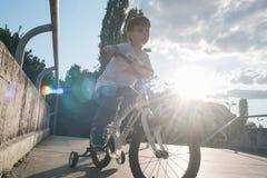 Criança com a bicicleta contra o sol Imagem de Stock