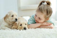 Criança com cachorrinhos de Labrador em casa no tapete imagens de stock royalty free