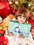 Criança com a caixa de presente perto da árvore de Natal. Fotografia de Stock