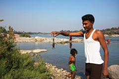 A criança com captura do pai crabs pelas mãos no rio Imagem de Stock